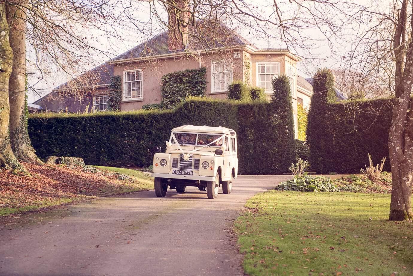 Classic Land Rover wedding car leaves Plush Manor wedding venue in Dorset