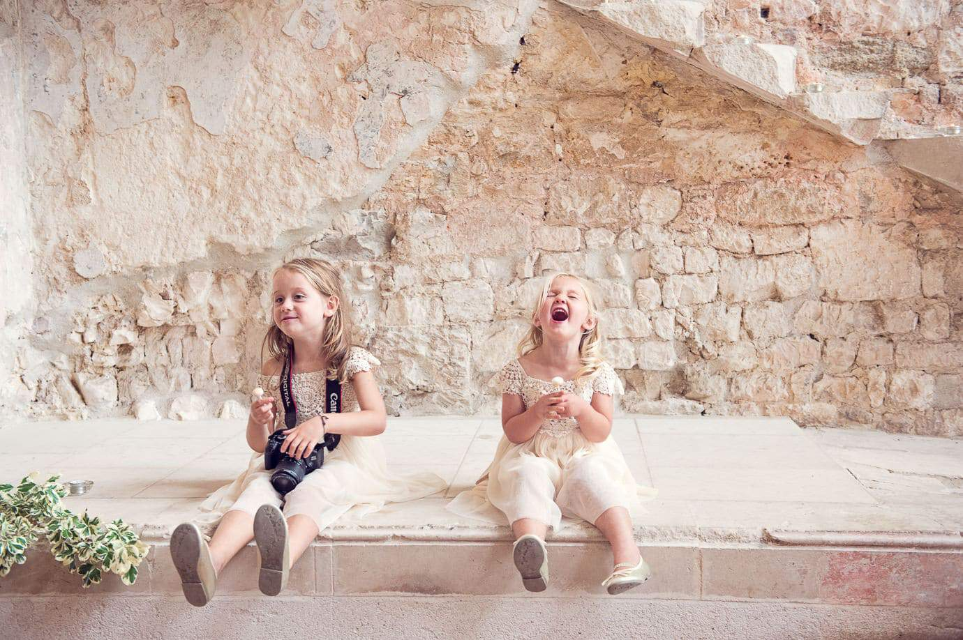 Flower girls laughing against stone walls of Lulworth Castle wedding venue in Dorset