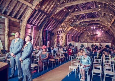 Groom and best man wait for bride in medieval barn wedding in Dorset