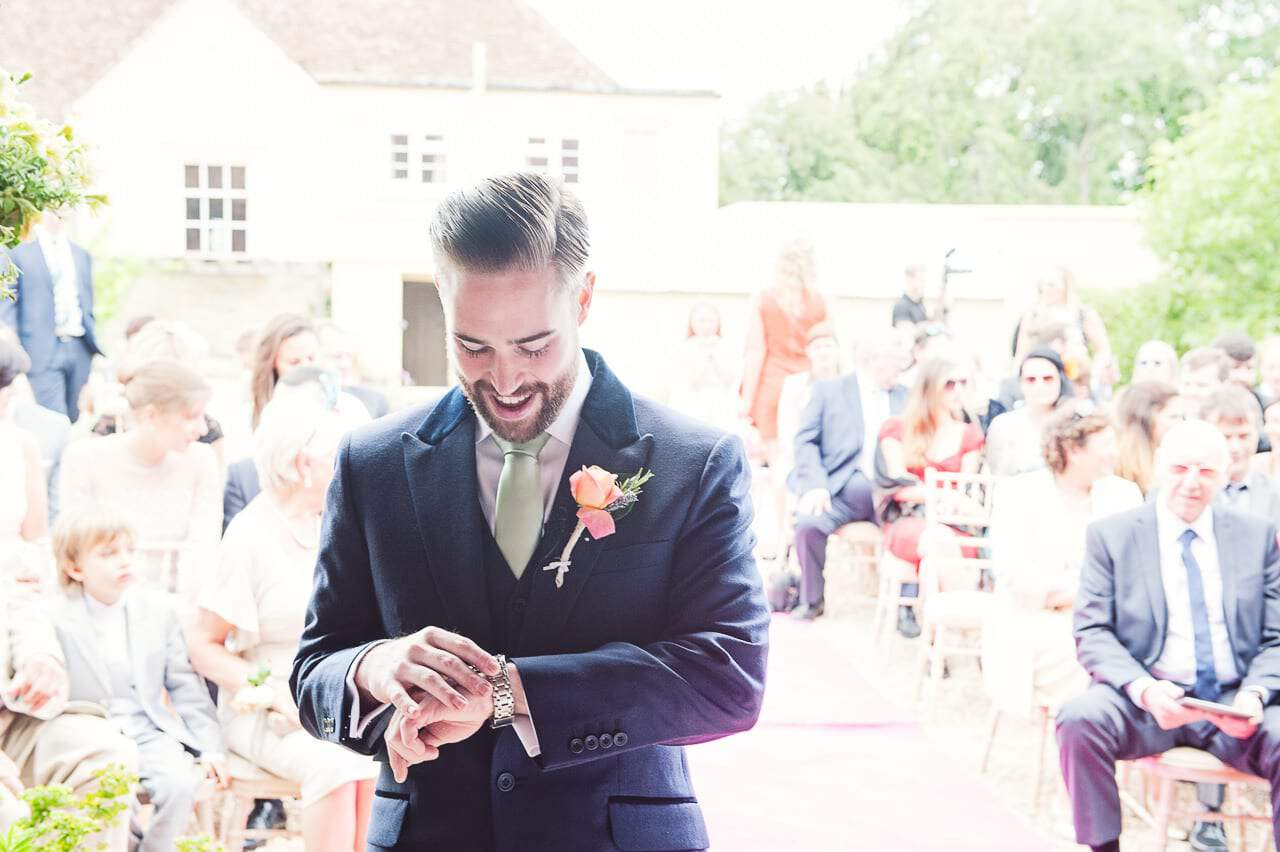 Groom checks his watch waiting for bride at outdoor wedding ceremony