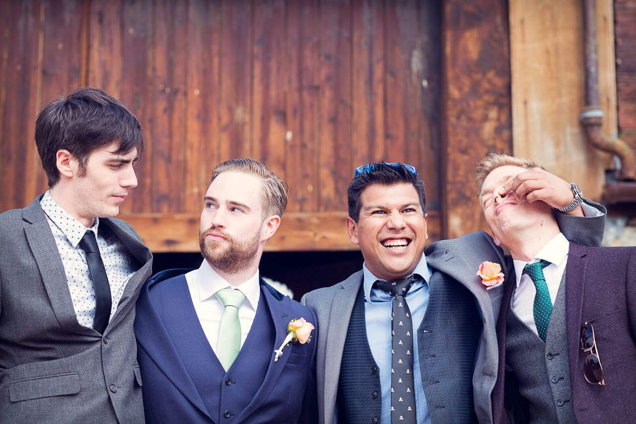 Groomsmen having fun at Stockbridge Farm Barn wedding venue