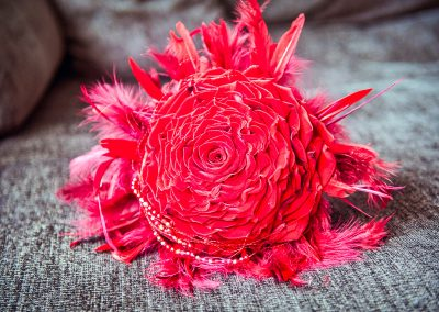 Huge red wedding flower bouquet with feathers and beads at Sandbanks Hotel wedding