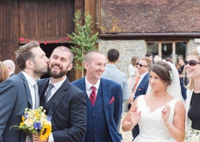 Male wedding guests kiss at Stockbridge Farm Barn wedding venue