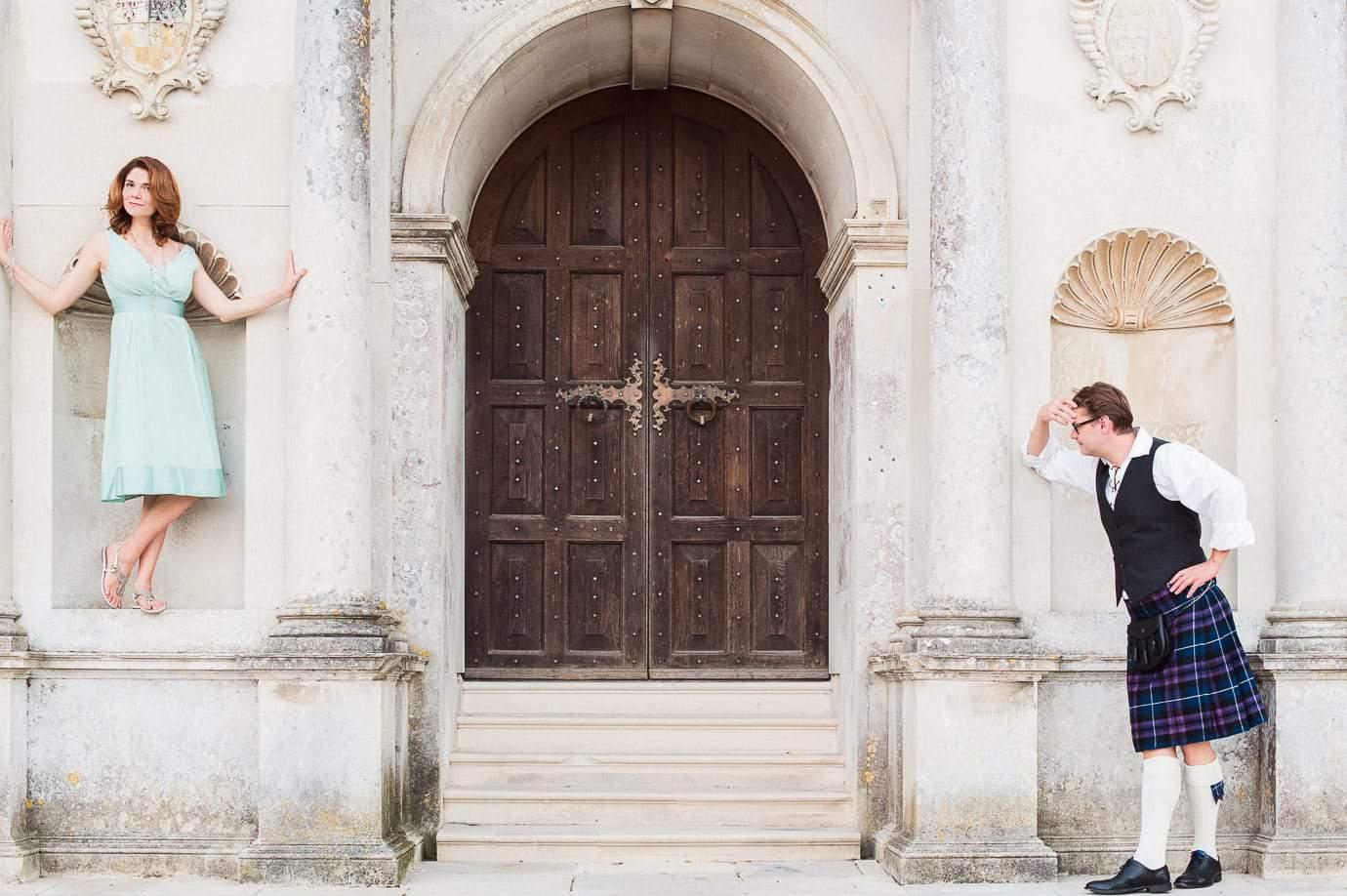 Fun wedding guests posing at Lulworth Castle wedding venue grand wooden doors