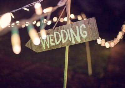 Wooden wedding direction sign at night with LED fairy lights at Plush Manor wedding