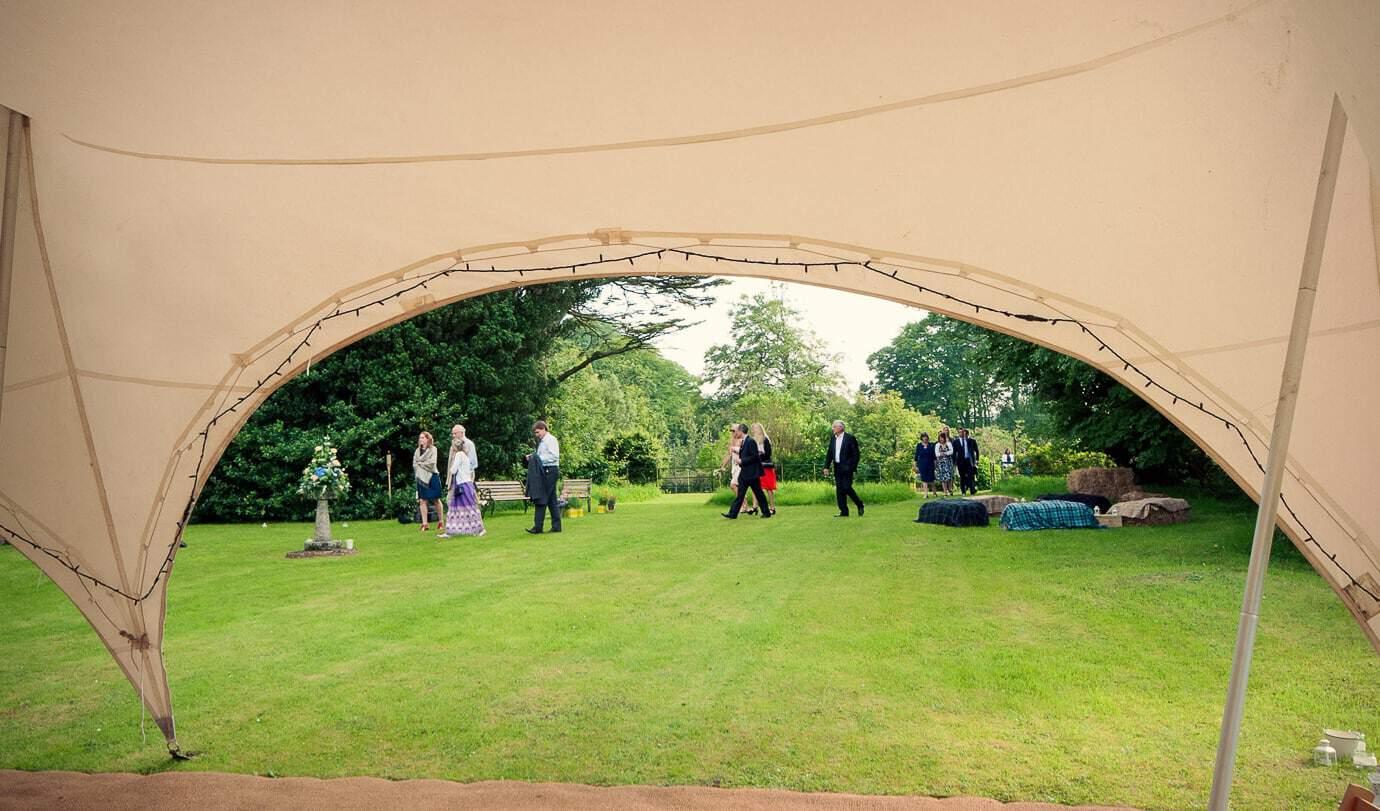 Plush Manor wedding guests walk across gardens to wedding breakfast in church