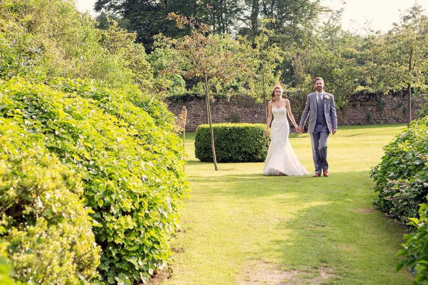 Plush Manor wedding photographers capture bride and groom walking in gardens