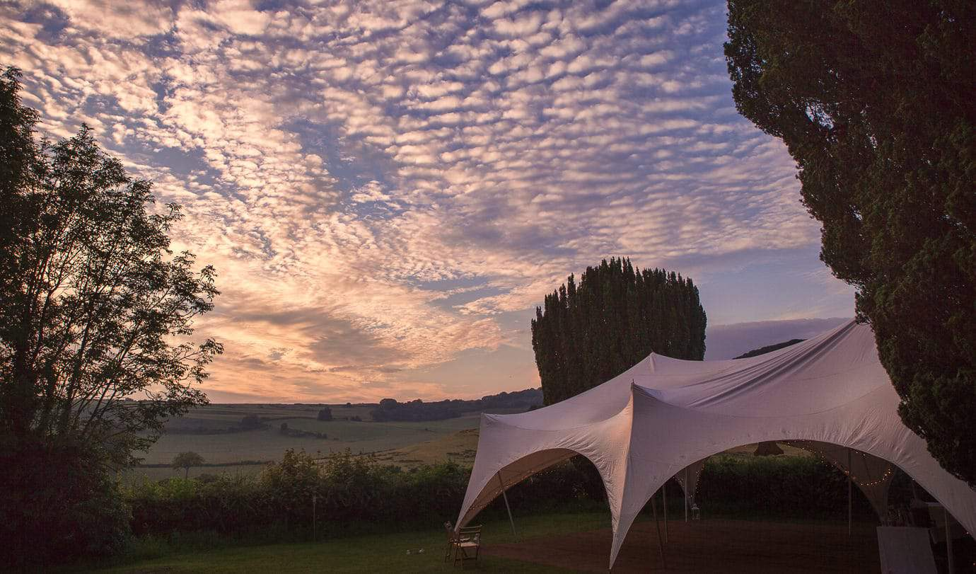 Plush Manor wedding venue stretch tent with sunset over Dorset countryside