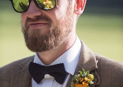 Reflection of bride in groom's mirrored sunglasses at Countryside wedding venue