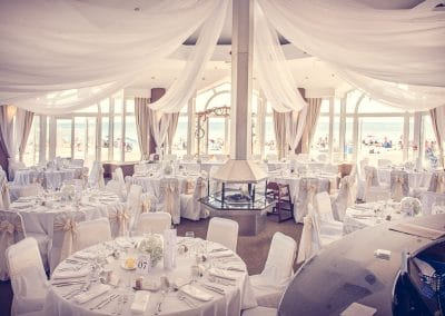 Sandbanks Hotel compass room wedding decoration with white drapes by beach