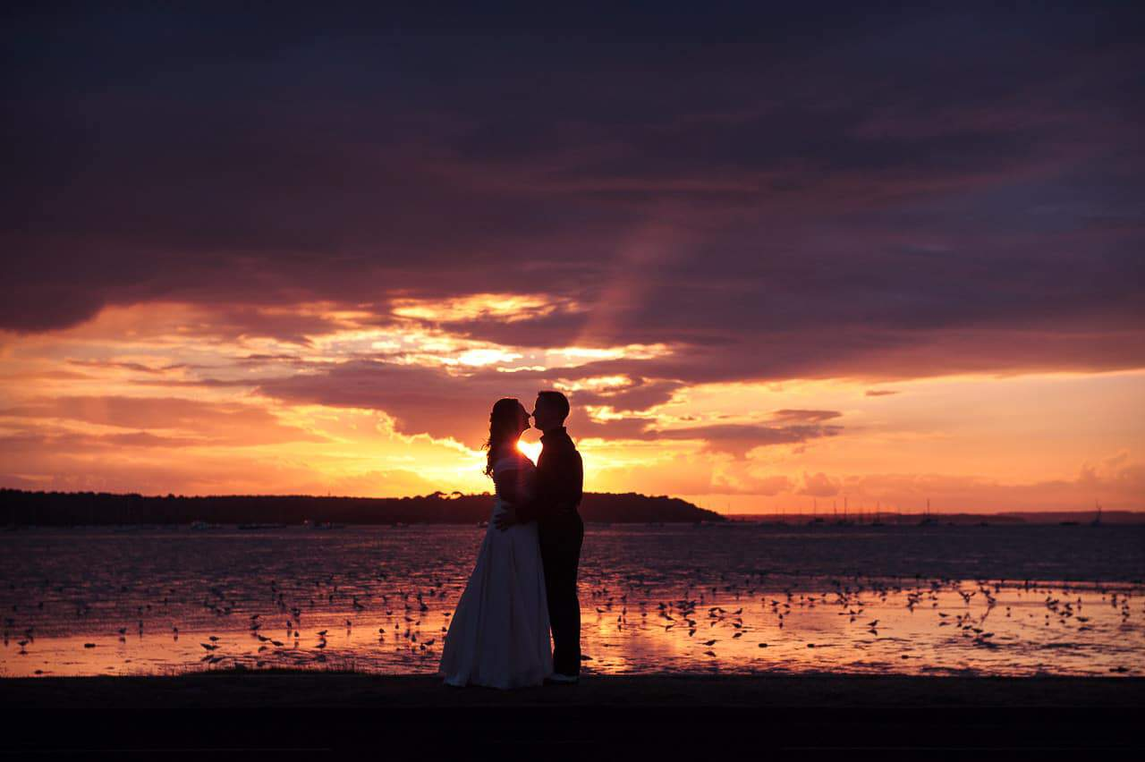 Sandbanks Hotel Wedding Photographers capture sunset over sea wedding kiss