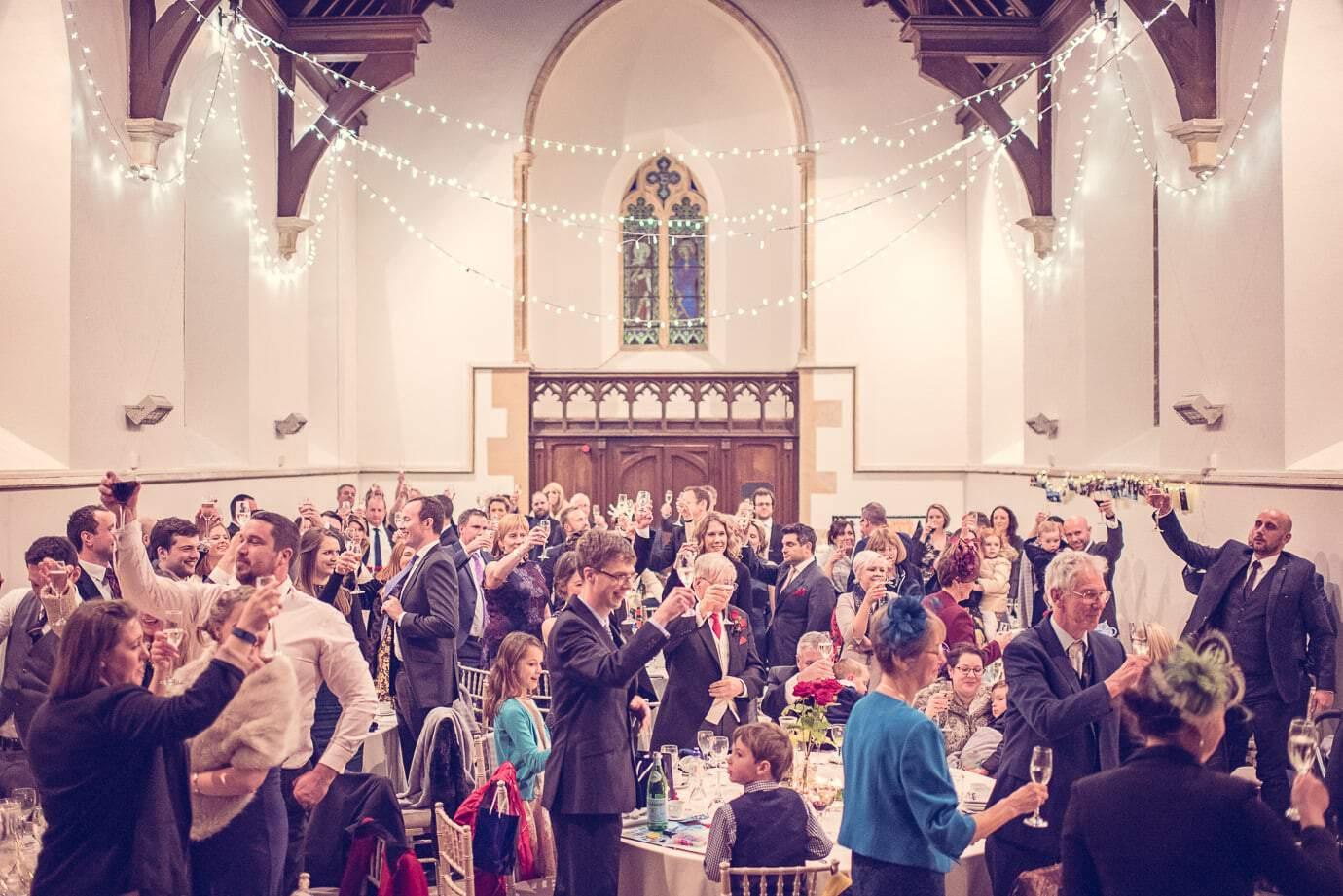 Wedding breakfast toasts inside church at Plush Manor wedding in Dorset