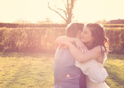 Wedding couple hugging in the countryside sun at Stockbridge Barn