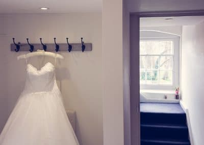 Wedding dress hangs next to Avon suite doorway at Sopley Mill wedding photographs