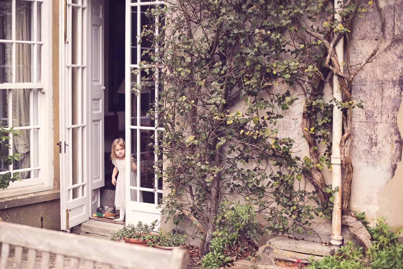 Wedding flower girl peers around door at Plush Manor Dorset wedding venue
