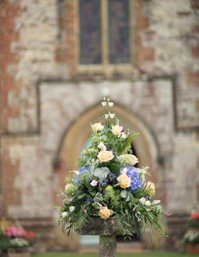 Wedding flower spray in stone bird bath outside Plush Manor Church venue