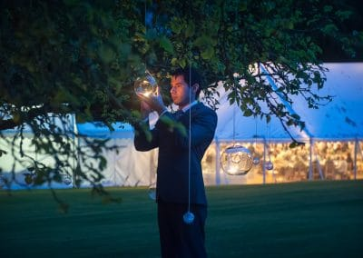 Wedding guest lights candles hanging from trees at Plush Manor marquee wedding