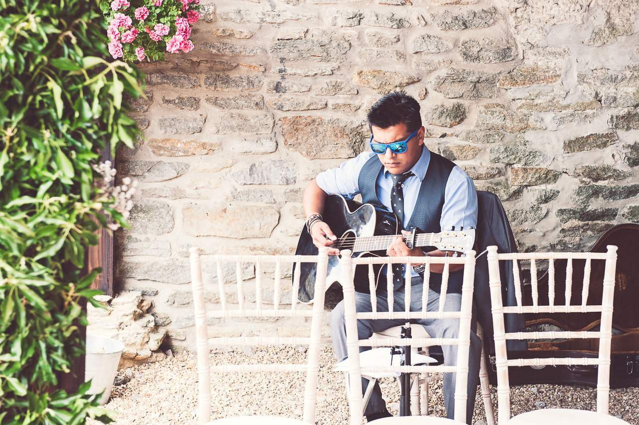 Wedding guest plays guitar at Stockbridge Farm Barn wedding ceremony