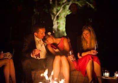 Wedding guests cuddle by bonfire outside Plush Manor Wedding Venue