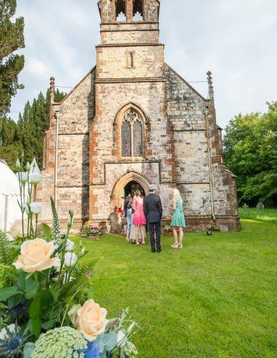 Wedding guests queue for wedding breakfast in Plush Manor stone church