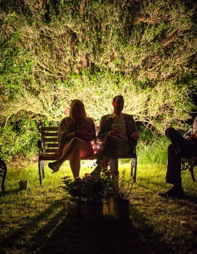 Wedding guests silhouettes sit in front of illuminated yew tree at Plush Manor church