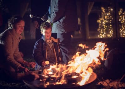 Wedding guests toast marshmallow in fire pit at Plush Manor wedding venue
