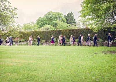 Wedding guests walk through Plush Manor gardens to The Folly wedding ceremony