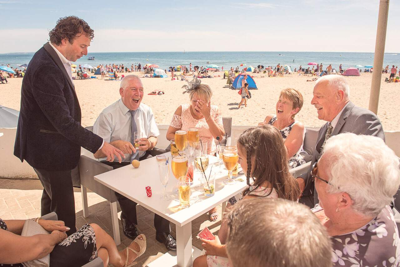 Wedding magician entertains Sandbanks Hotel wedding guests by the beach