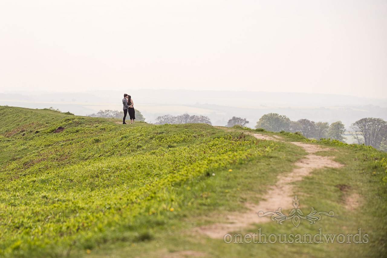 Couple stop for kiss during Badbury Rings Engagement Photographs