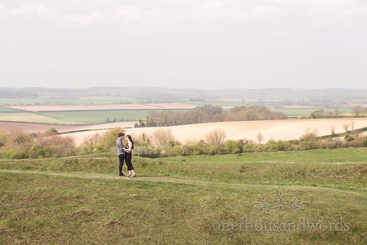 Engaged couple embrace a top of rampart at Badbury Rings Engagement Photographs