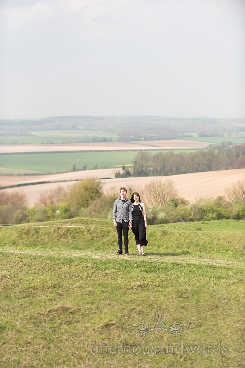 Engaged couple hold hands on top of rampart at Badbury Rings Engagement Photographs
