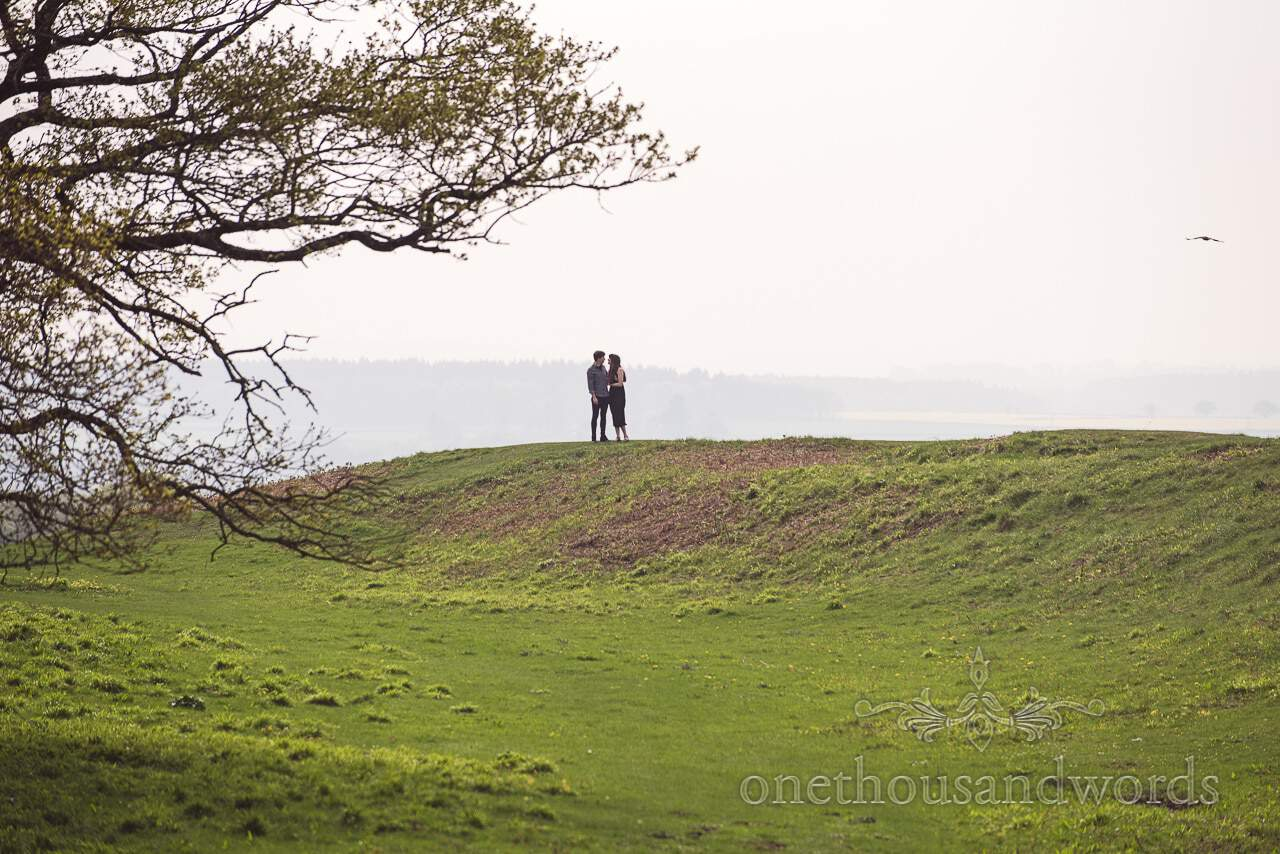Engaged couple on to of rampart at Badbury Rings Engagement Photographs