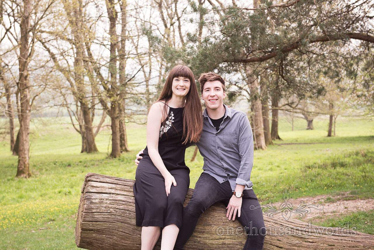 Engagement couple seated on fallen tree at Badbury Rings Engagement Photographs