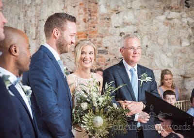 Beaming bride stands next to groom for first time at Lulworth Castle Wedding