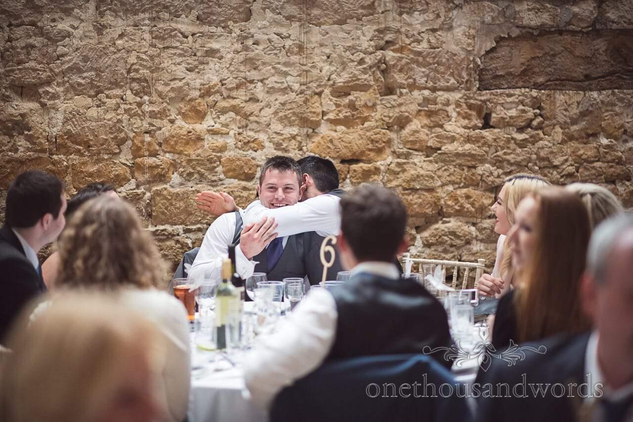 Best man gets a hug from groomsman at Tithe Barn Symondsbury Wedding