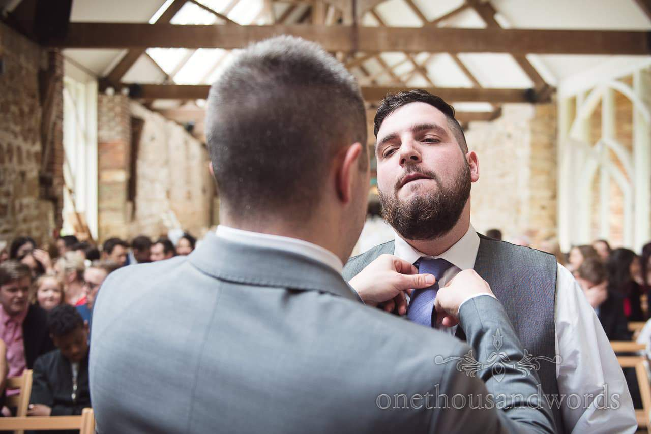 Best man helps groom with tie before at the Tithe Barn Symondsbury Wedding