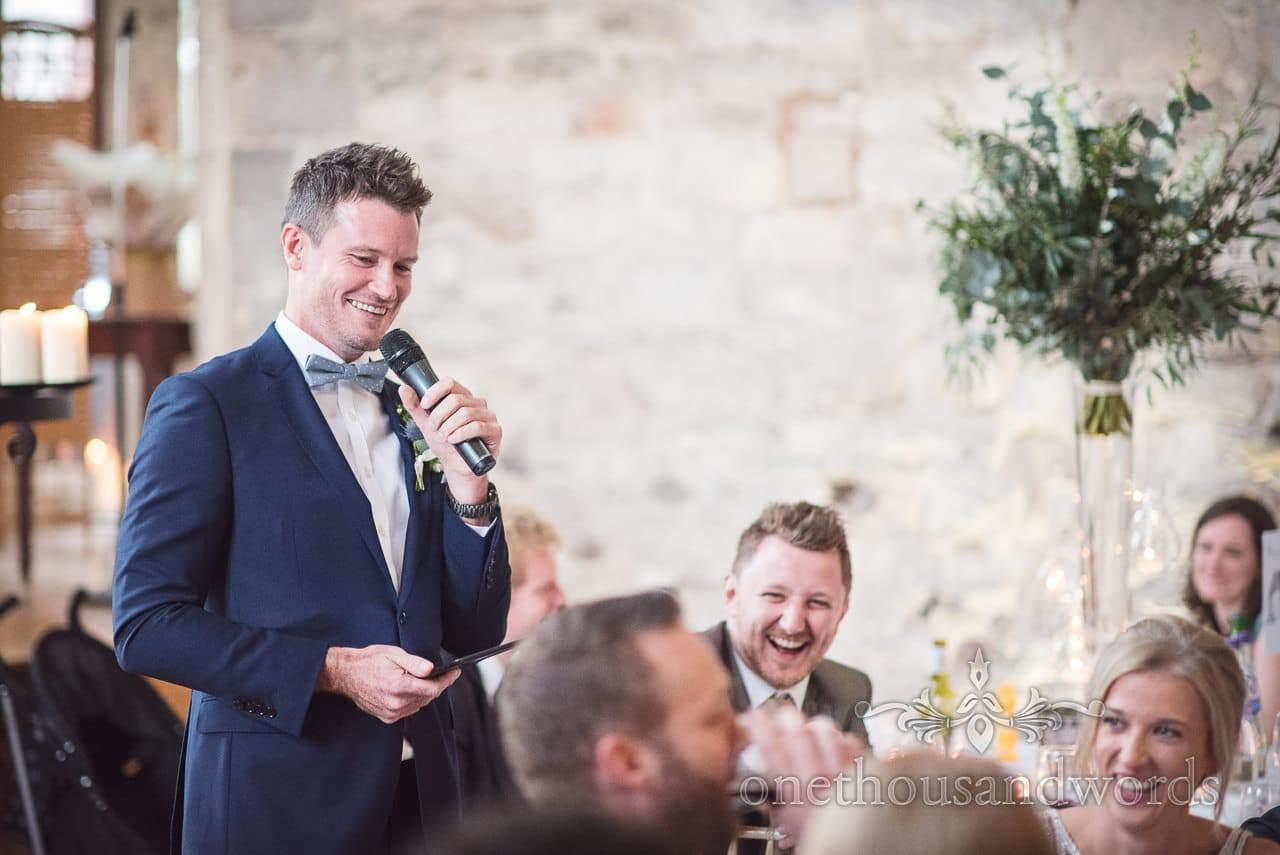 Best man in bow tie makes speech at Lulworth Castle Wedding venue in Dorset