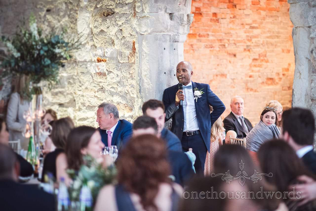 Best man makes speech against stone walls at Lulworth Castle Wedding