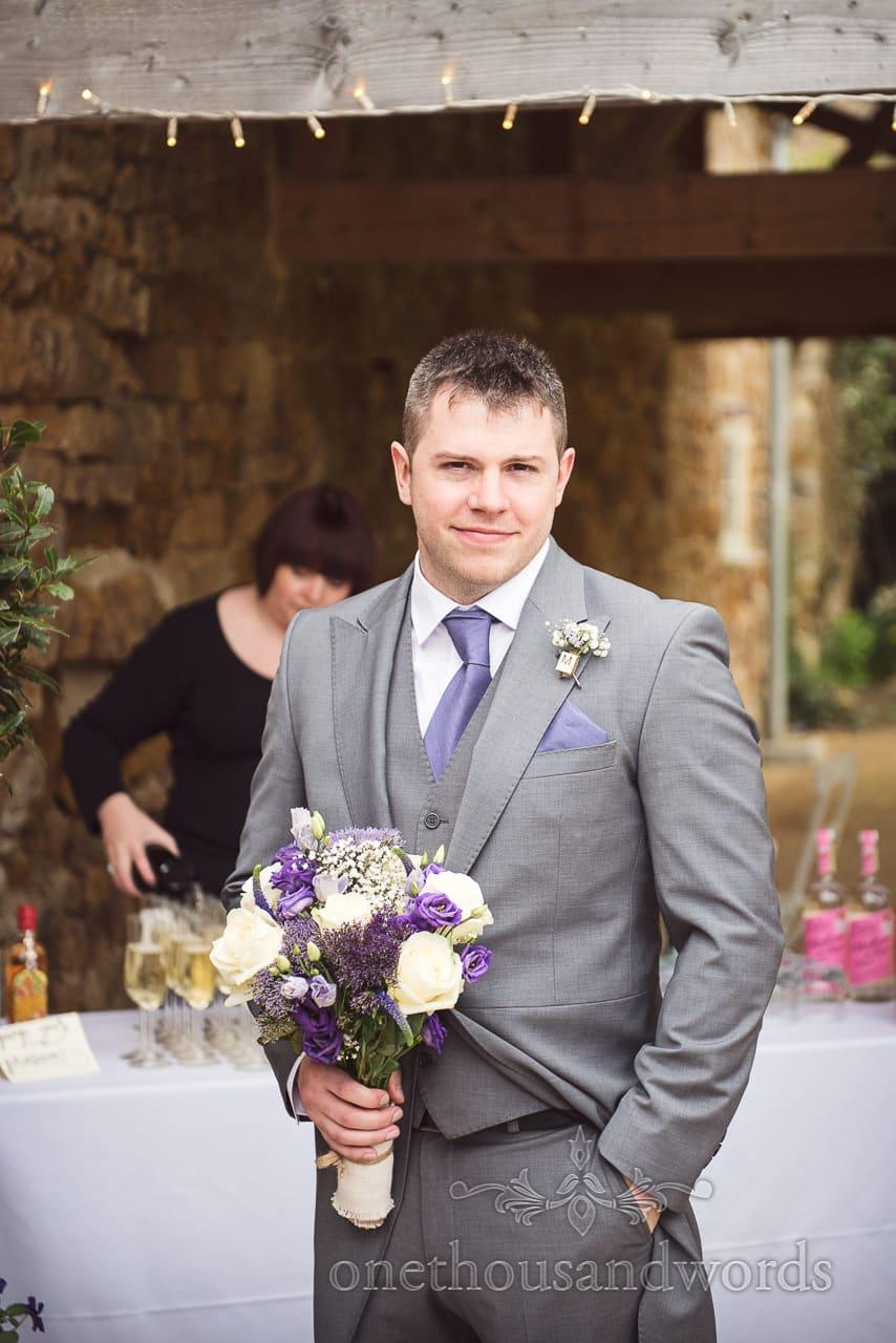 Best man with bridal bouquet at Tithe Barn Symondsbury Wedding