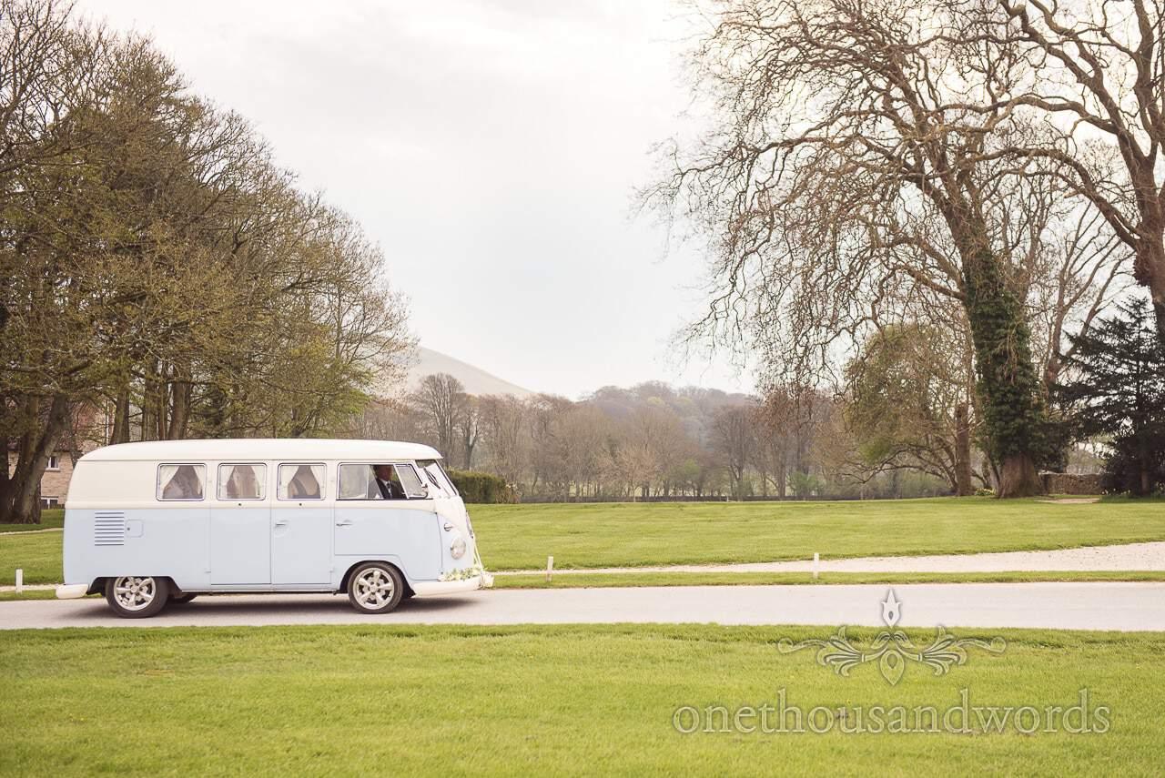 Blue VW split screen wedding van drives through Lulworth Castle countryside grounds