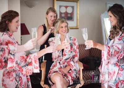 Bride and bridesmaids share a toast on morning of Lulworth Castle Wedding Photos