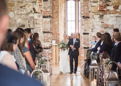 Bride and father enter Lulworth Castle Wedding ceremony through brick doorway