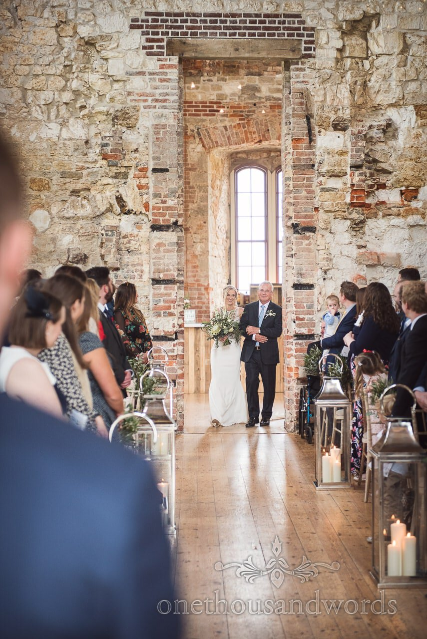 Bride and father enter Lulworth Castle Wedding ceremony through brick doorway