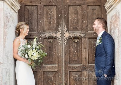 Bride and groom against huge wooden doors at Lulworth Castle Wedding Venue