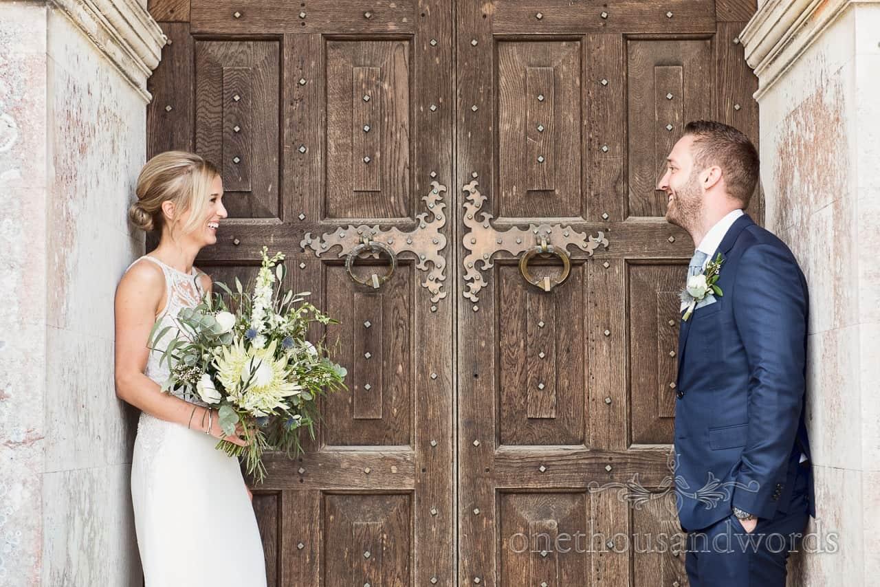 Bride and groom against huge wooden doors at Lulworth Castle Wedding Venue