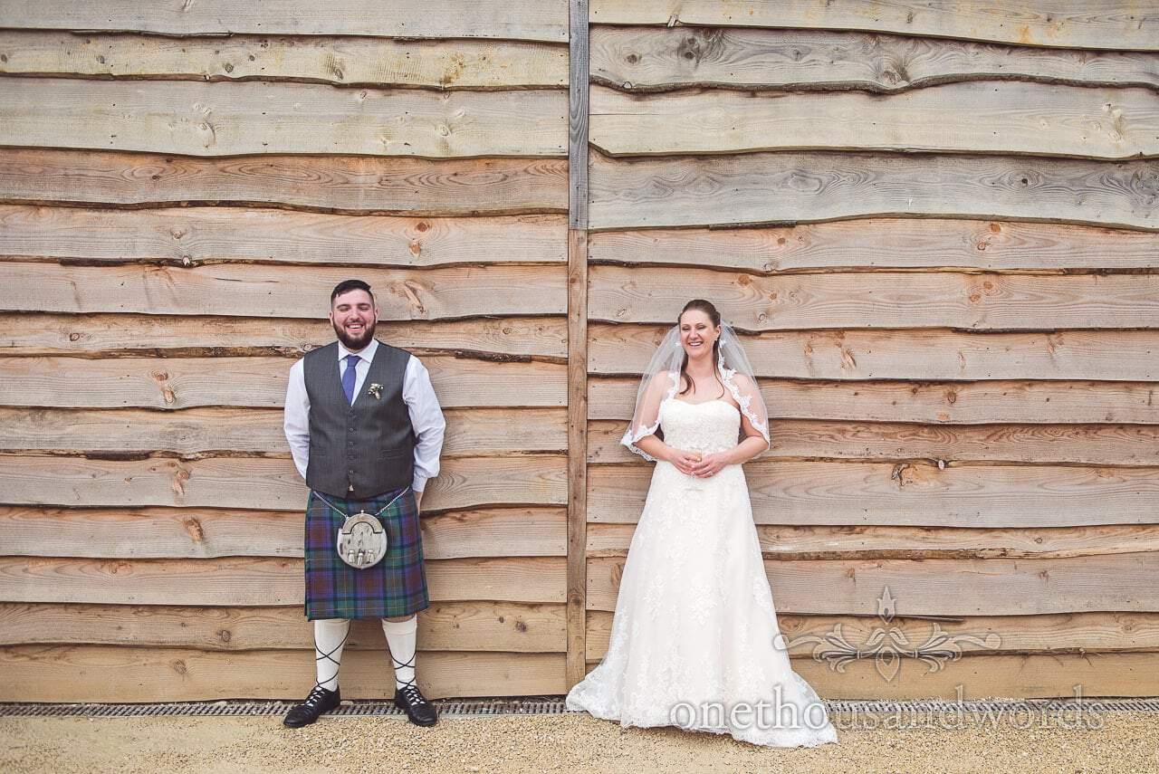 Bride and groom against wood clad wall at Tithe Barn Symondsbury Wedding