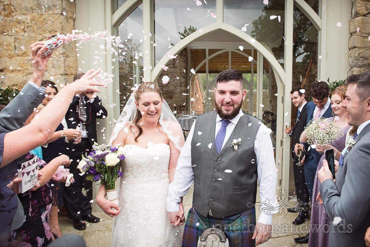 Bride and groom are showered with confetti at Tithe Barn Symondsbury Wedding