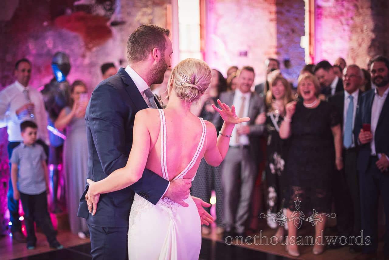 Bride and groom beckon wedding guests onto dance floor at Lulworth Castle Wedding
