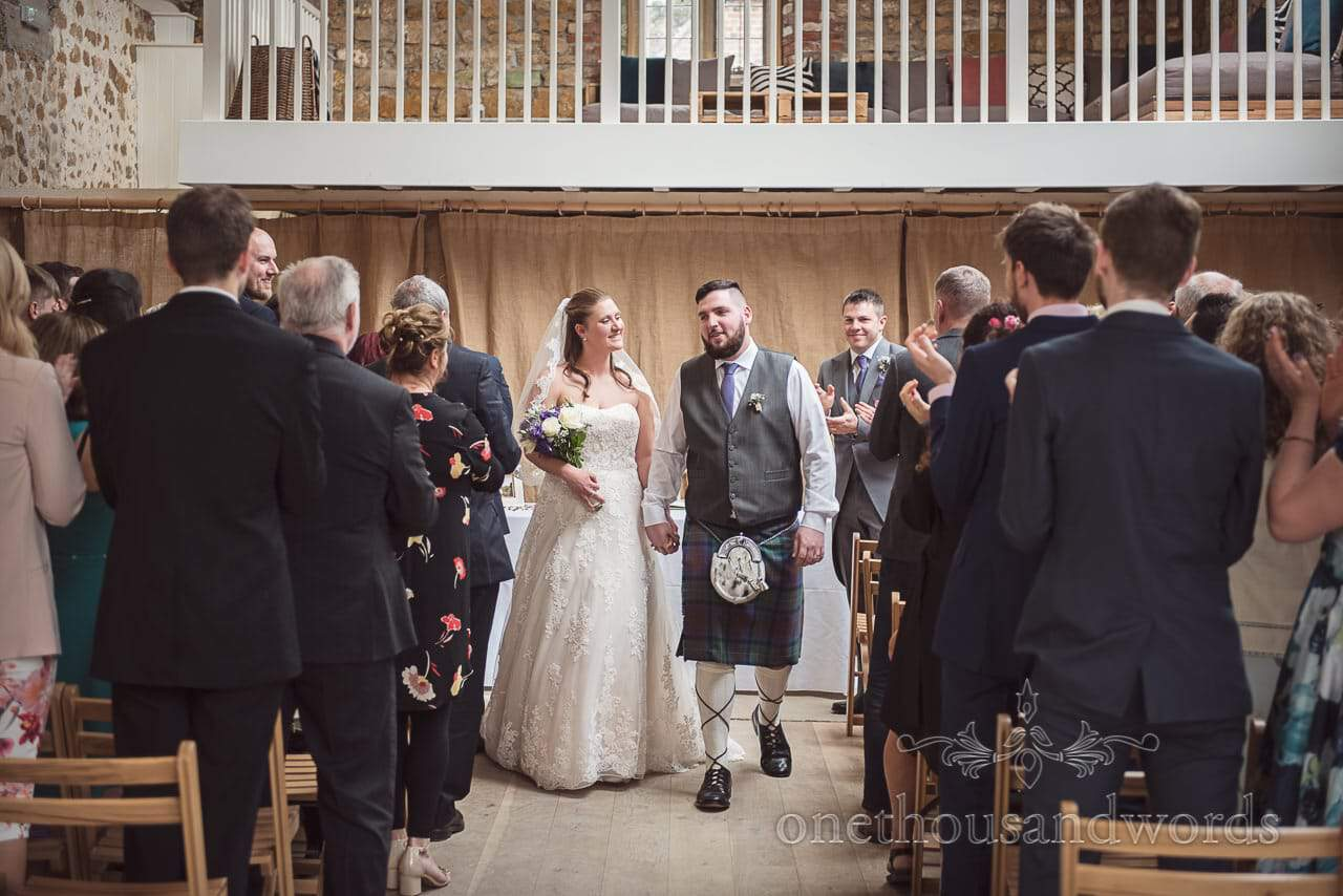 Bride and groom come back down the aisle as husband and wife at Tithe Barn Symondsbury Wedding