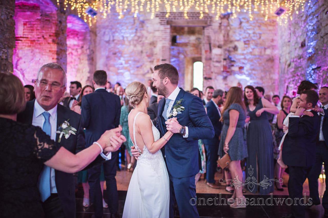 Bride and groom dance under disco lighting at Lulworth Castle Wedding Photos